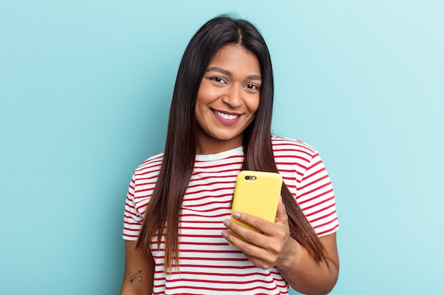 Young venezuelan woman holding mobile phone isolated on blue background happy, smiling and cheerful.