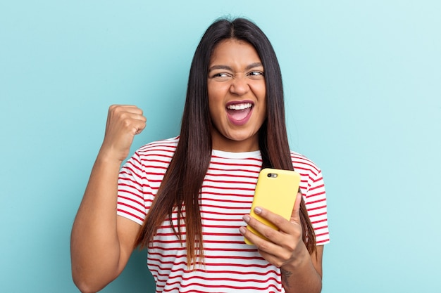 Young venezuelan woman holding mobile phone isolated on blue background raising fist after a victory, winner concept.