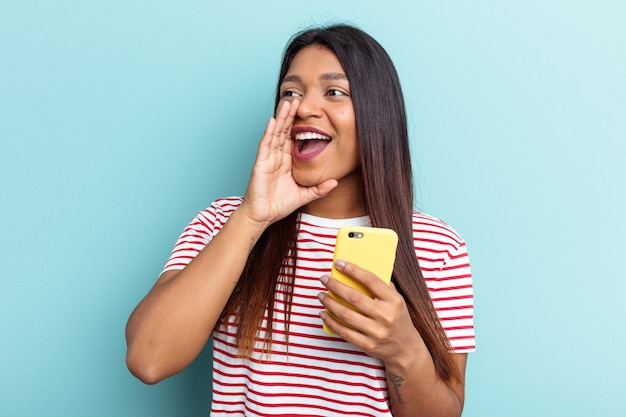 Young venezuelan woman holding mobile phone isolated on blue background shouting and holding palm near opened mouth.