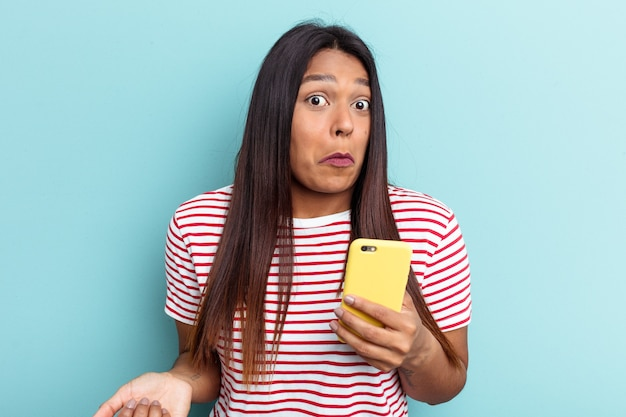 Young venezuelan woman holding mobile phone isolated on blue background shrugs shoulders and open eyes confused.