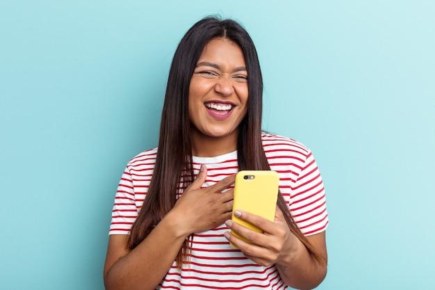 Молодая венесуэльская женщина, держащая мобильный телефон на синем фоне, громко смеется, держа руку на груди.