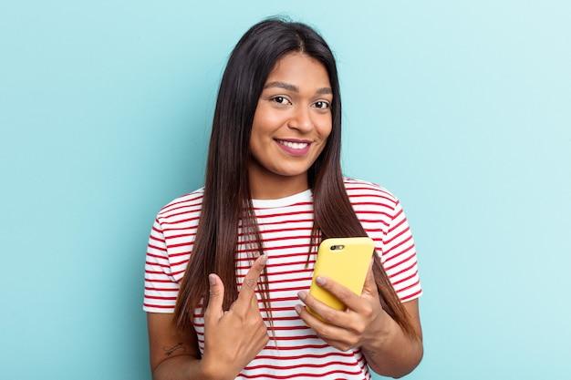 青い背景で隔離された携帯電話を持っている若いベネズエラの女性は、招待が近づくようにあなたに指を指しています。