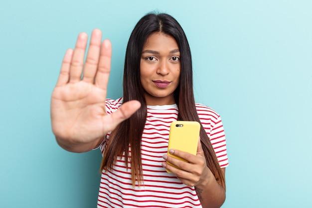 青い背景で隔離の携帯電話を保持している若いベネズエラの女性は、一時停止の標識を示す伸ばした手で立って、あなたを防ぎます。