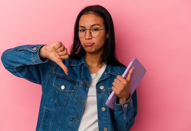 Young venezuelan woman holding a tablet isolated on pink background showing a dislike gesture, thumbs down. disagreement concept.