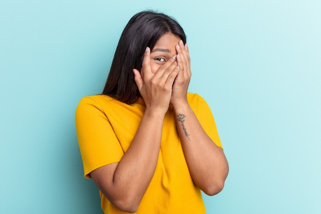Young venezuelan woman isolated on blue background blink through fingers frightened and nervous.