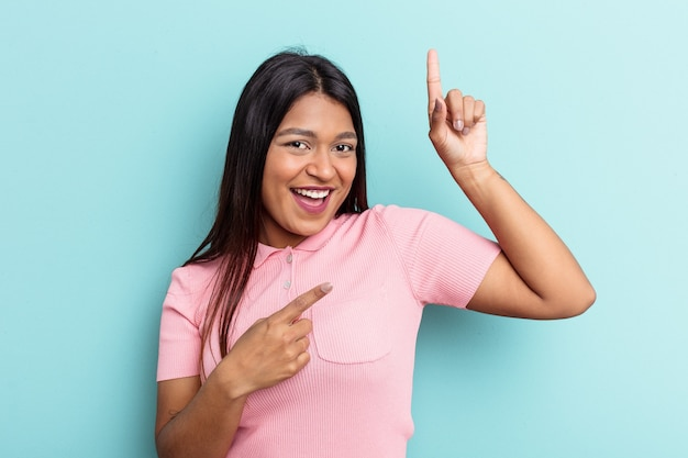 Young venezuelan woman isolated on blue background dancing and having fun.