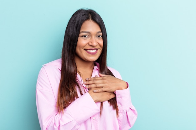 Young venezuelan woman isolated on blue background has friendly expression, pressing palm to chest. love concept.