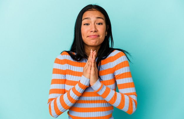 Young venezuelan woman isolated on blue background holding hands in pray near mouth, feels confident.