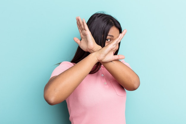 Young venezuelan woman isolated on blue background keeping two arms crossed, denial concept.