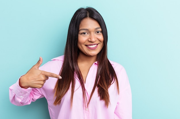 Young venezuelan woman isolated on blue background person pointing by hand to a shirt copy space, proud and confident