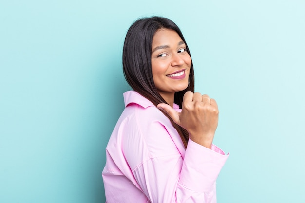 Young venezuelan woman isolated on blue background points with thumb finger away, laughing and carefree.