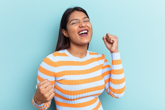 Young venezuelan woman isolated on blue background raising fist after a victory, winner concept.