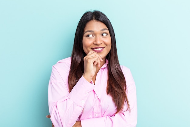 Young venezuelan woman isolated on blue background relaxed thinking about something looking at a copy space.