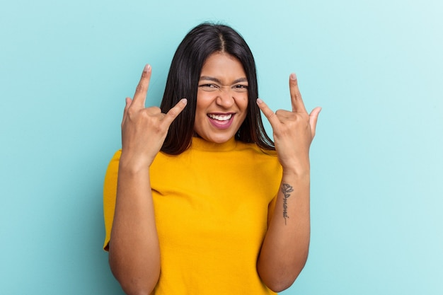 Young venezuelan woman isolated on blue background showing a horns gesture as a revolution concept.
