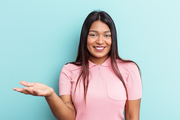 Young venezuelan woman isolated on blue background showing a welcome expression.