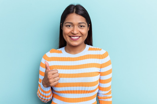 Young venezuelan woman isolated on blue background smiling and raising thumb up