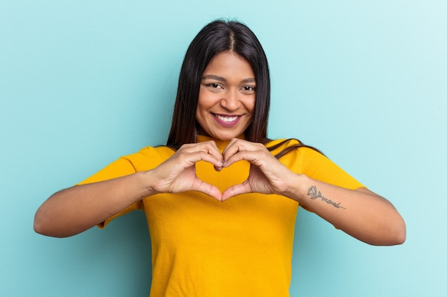 Young venezuelan woman isolated on blue background smiling and showing a heart shape with hands.