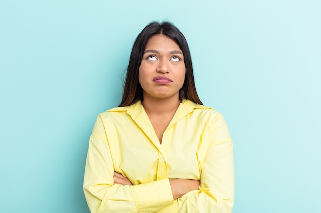 Young venezuelan woman isolated on blue background tired of a repetitive task.