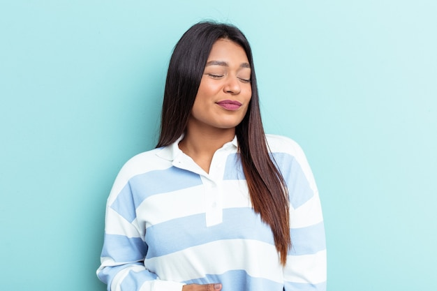 Young venezuelan woman isolated on blue background touches tummy, smiles gently, eating and satisfaction concept.