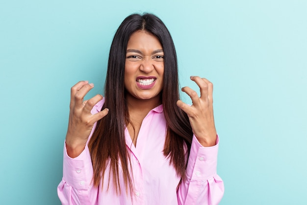 Young venezuelan woman isolated on blue background upset screaming with tense hands.