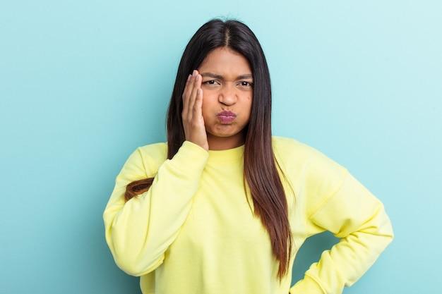 青い背景に分離された若いベネズエラの女性は頬を吹く、疲れた表情をしています。表情のコンセプト。