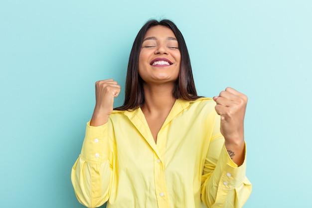 勝利、情熱と熱意、幸せな表現を祝う青い背景に分離された若いベネズエラの女性。