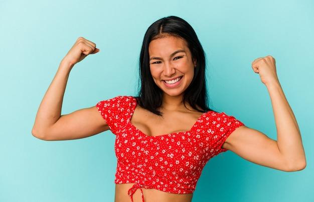 青の背景に孤立した若いベネズエラの女性は、のんびりと興奮して応援しています。勝利の概念。