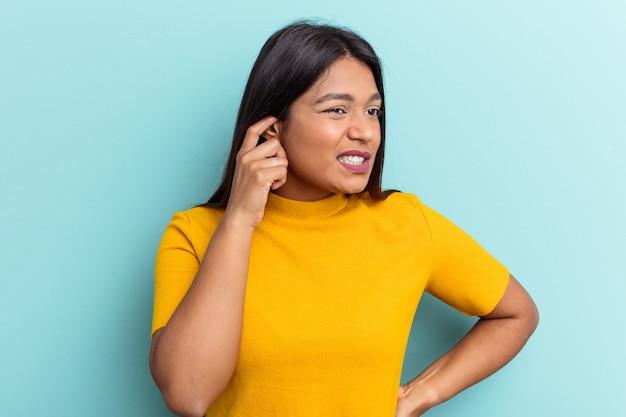 手で耳を覆う青い背景に分離された若いベネズエラの女性。