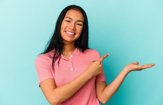 青い背景に分離された若いベネズエラの女性は、手のひらにコピースペースを持って興奮しました。