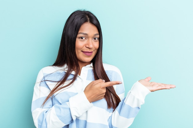 青い背景に孤立した若いベネズエラの女性は、手のひらにコピースペースを持って興奮しました。