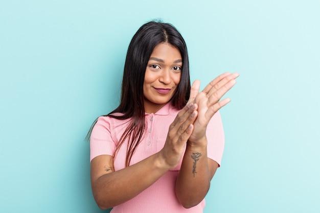 青い背景に孤立した若いベネズエラの女性は、エネルギッシュで快適に感じ、自信を持って手をこすります。