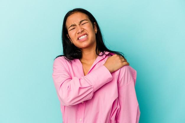 肩の痛みを持っている青い背景に分離された若いベネズエラの女性。