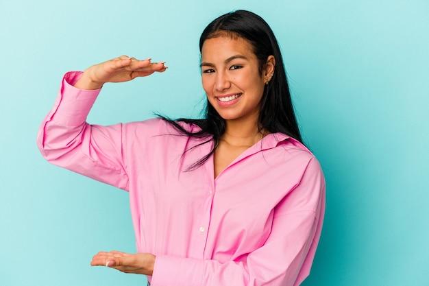 青の背景に孤立した若いベネズエラの女性は、人差し指で少し何かを持って、笑顔で自信を持っています。