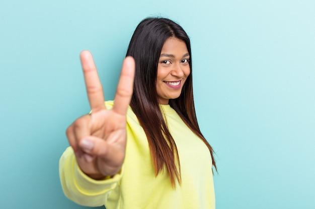 青の背景に孤立した若いベネズエラの女性は、指で平和のシンボルを示して楽しくてのんきです。