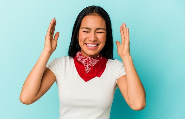 たくさん笑ってうれしそうな青い背景に孤立した若いベネズエラの女性。幸福の概念。