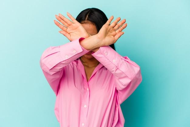 Молодая венесуэльская женщина, изолированные на синем фоне, держа скрещенными руками, концепцию отрицания.