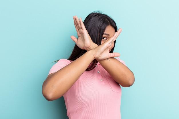 若いベネズエラの女性は、2つの腕を交差させたまま、青い背景で隔離、概念を否定します。