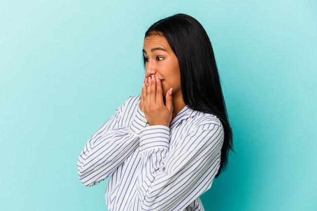 何かについて笑い、手で口を覆って、青い背景に孤立した若いベネズエラの女性。