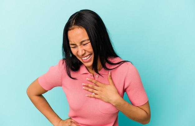 若いベネズエラの女性は、幸せの概念、心に手を置いて笑って青い背景に分離されました。
