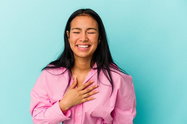 青い背景に孤立した若いベネズエラの女性は、胸に手を置いて大声で笑います。
