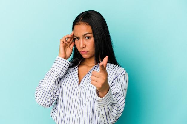 若いベネズエラの女性は、指で寺院を指して、考えて、タスクに焦点を当て、青い背景に分離されました。