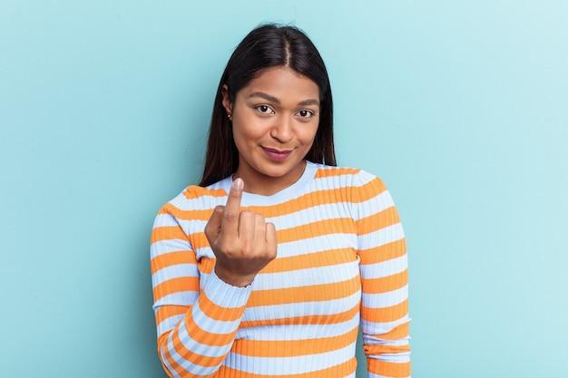 青い背景に孤立した若いベネズエラの女性は、招待が近づくようにあなたに指を指しています。