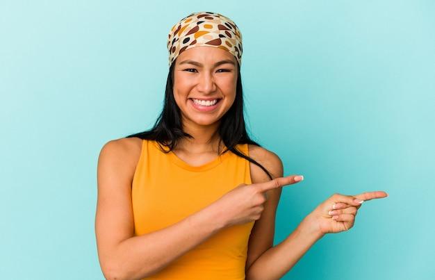 興奮と欲望を表現し、コピースペースに人差し指で指している青い背景に孤立した若いベネズエラの女性。