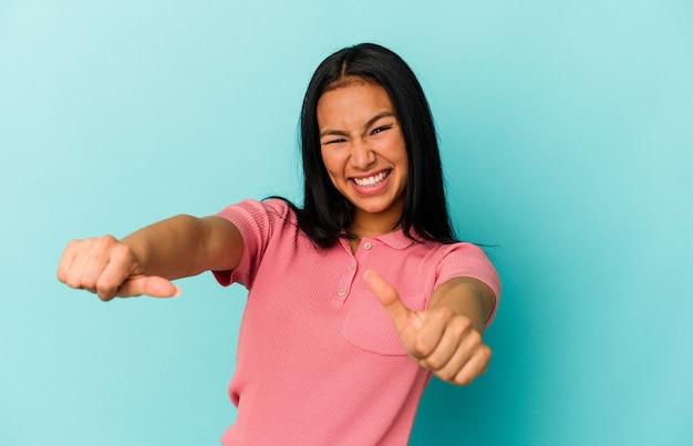 青い背景に孤立した若いベネズエラの女性は、両方の親指を上げて、笑顔で自信を持っています。