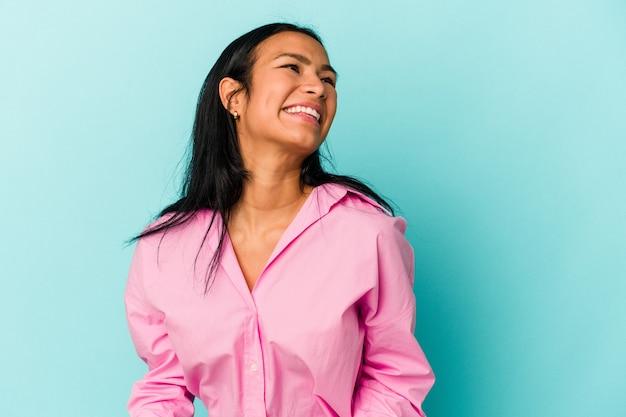 青い背景に分離された若いベネズエラの女性はリラックスして幸せな笑い、首を伸ばして歯を見せています。