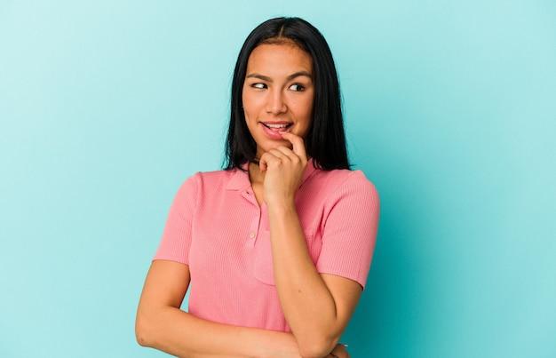 青い背景に孤立した若いベネズエラの女性は、コピースペースを見ている何かについて考えてリラックスしました。