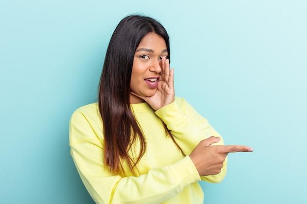 何かを報告する側を指して、ゴシップを言って青い背景に孤立した若いベネズエラの女性。