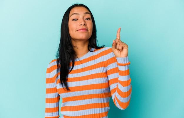 指でナンバーワンを示す青い背景に分離された若いベネズエラの女性。