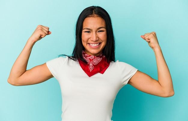 若いベネズエラの女性は、女性の力の象徴である腕で強さのジェスチャーを示す青い背景で隔離