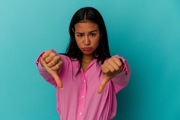若いベネズエラの女性は、親指を下に示し、嫌悪感を表現する青い背景で隔離。